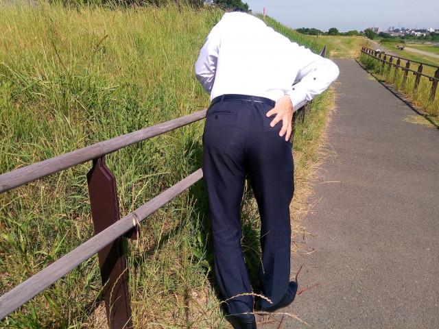 腰痛から柵にもたれる男性